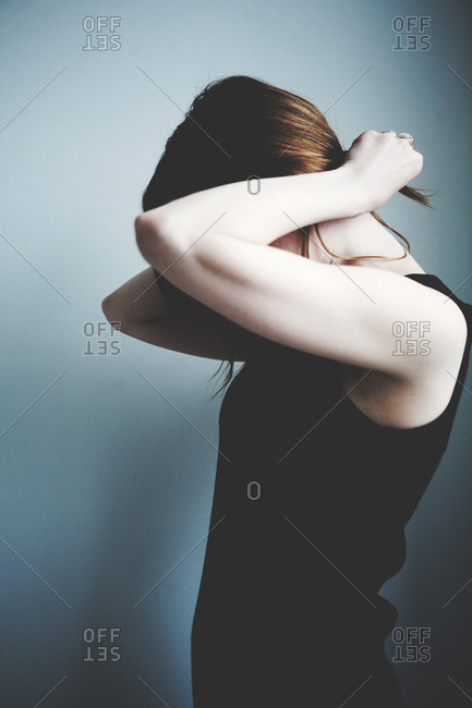 Young woman putting her hair in a ponytail