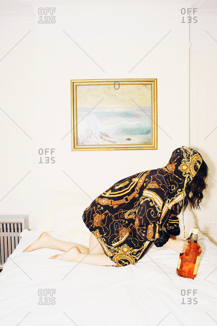 Woman in golden pattern hooded coat knees on bed with a bottle of alcohol