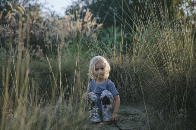 Little boy squatting among tall grass at Little Sahara State Park, USA
