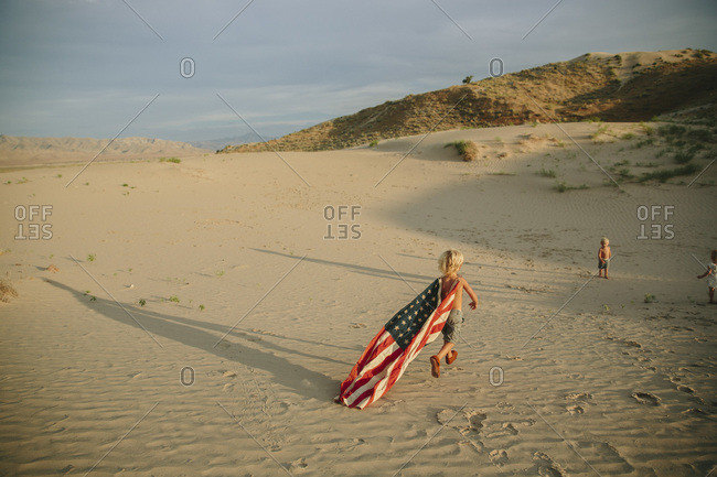 Boy running with American flag at Little Sahara State Park, USA