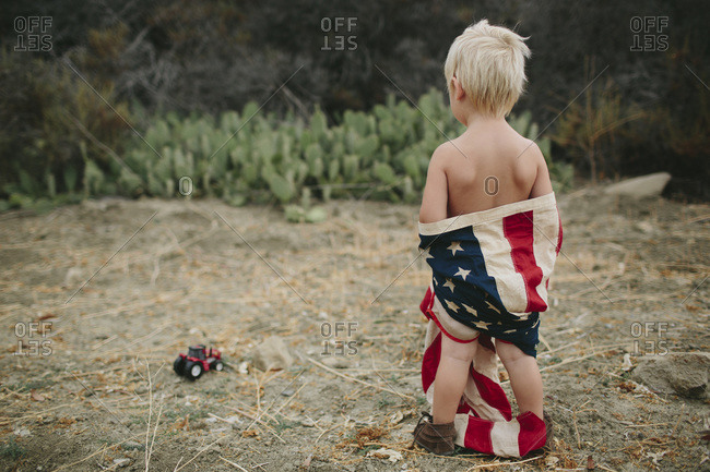Back view of boy wrapped in an American flag