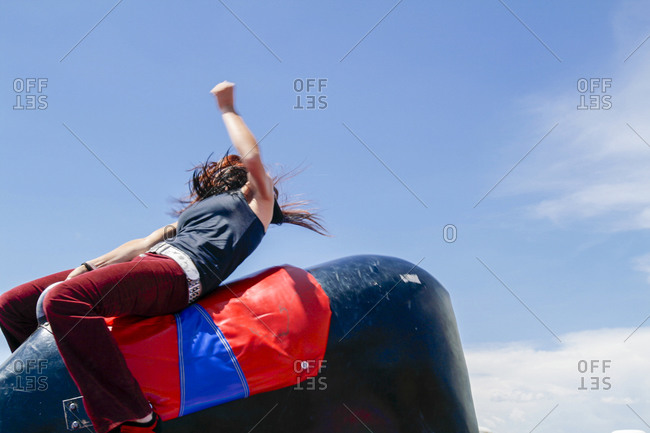 Woman riding a mechanical bull at a rodeo in Galisteo, New Mexico, USA