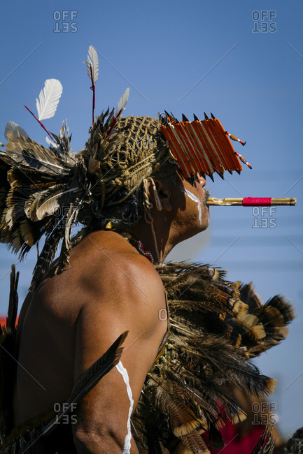 Native American Miwuk dancer blowing a pipe at the Gallup Intertribal ceremonies in New Mexico, USA