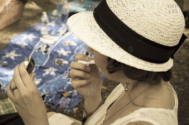 New York City, NY, USA - August 16, 2014: Woman applying make up at Jazz Age Lawn Party at Governors Island