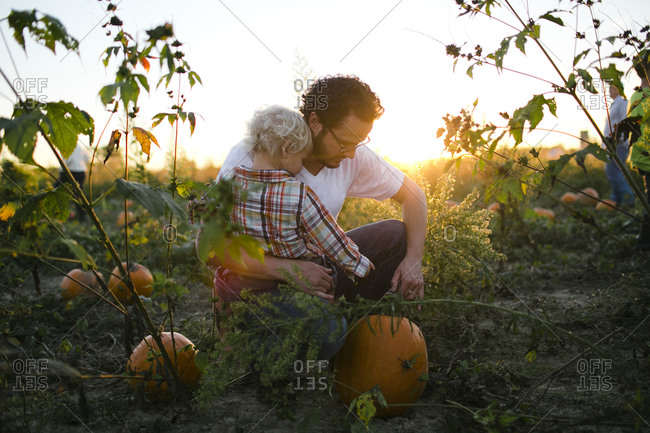 Father and son choosing a Halloween pumpkin in a field