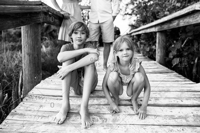 Siblings sitting on jetty while their parents standing in the background