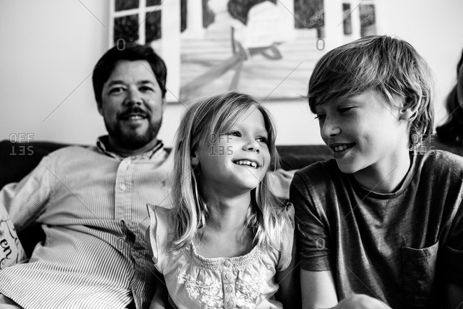 Father with his daughter and son sitting on couch