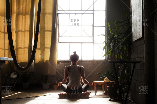 Young woman meditating in a loft apartment