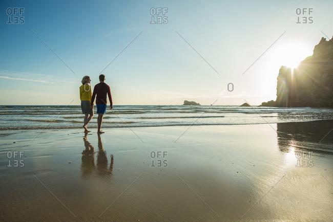 Teenage couple on the beach walking on the beach