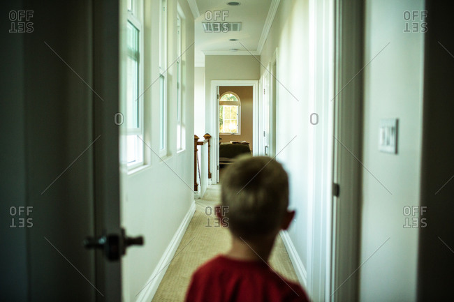 Back view of boy standing in a hallway