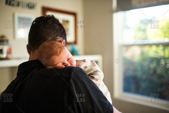 Newborn baby napping on his father's shoulder