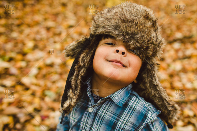 Portrait of a boy wearing an ushanka in an autumn forest