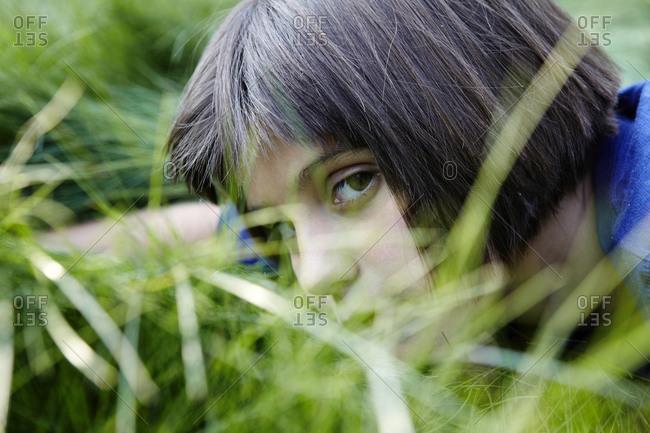 Portrait of a girl peeking through grass