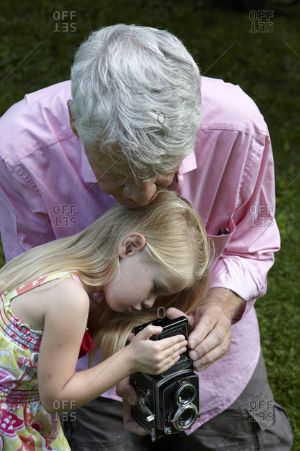 Old man holding a vintage camera with his granddaughter