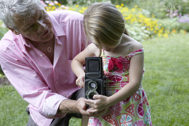Elderly man teaching his granddaughter how to use a vintage camera