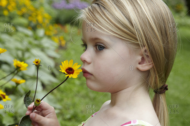 Young girl smelling a yellow daisy