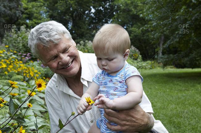 Elderly man holding his grandson in a garden