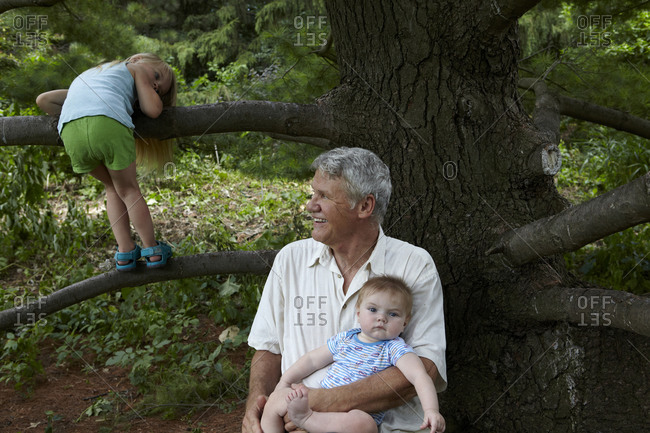 Elderly man holding his grandson at a tree