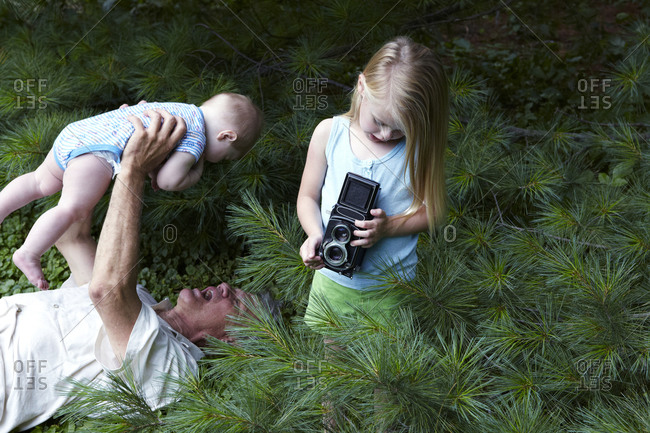 Young girl holding a vintage camera while his grandfather playing with her brother