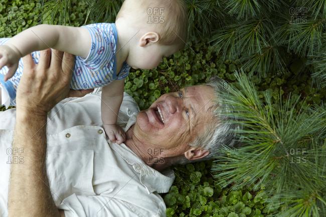 Elderly man holding his grandson