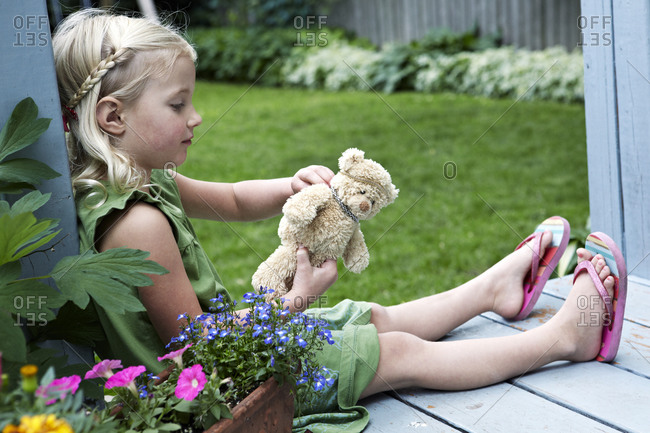 Girl playing with a teddy bear outdoors