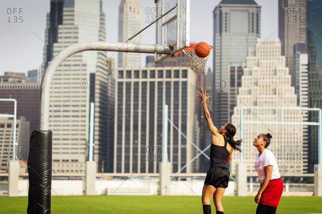 Young woman shooting a basketball into a hoop