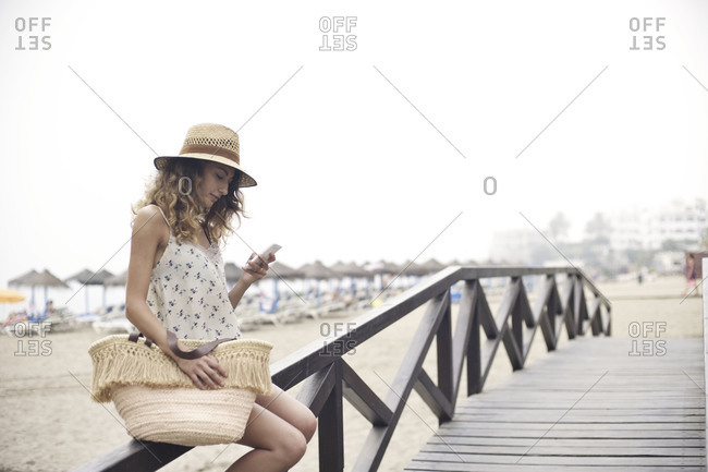 Woman texting on wooden bridge