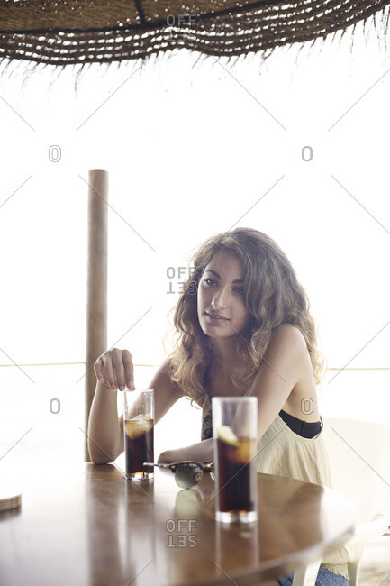 Woman sitting in bar of tropical resort