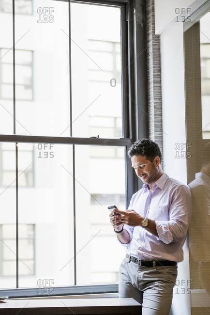 A man in an office checking his smart phone.