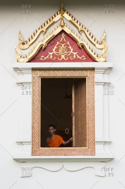 Chiang Mai, Thailand - January 18, 2013: A monk closes the window shutters at Wat Phra Singh temple in Chiang Mai, Thailand