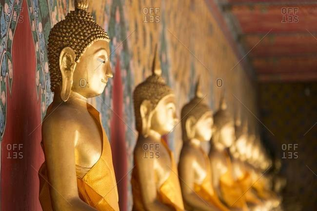 A row of Buddha statues at the Wat Arun temple in Bangkok, Thailand