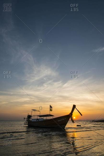 A long-tail fishing boat sits on the beach at sunset in Krabi, Thailand