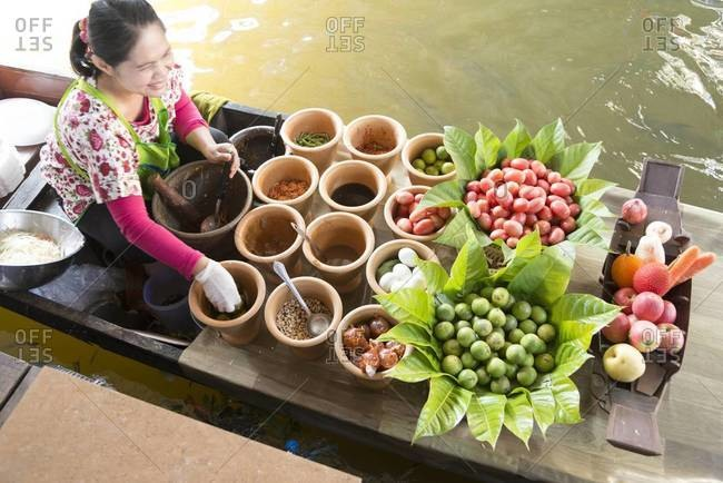 Bangkok, Thailand - January 12, 2014: A woman in a boat cooks food at the Taling Chan floating market in Bangkok, Thailand