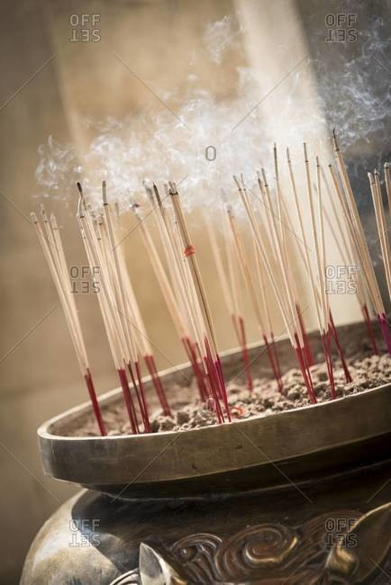 Incense sticks in a large pot at a temple in Ayutthaya, Thailand