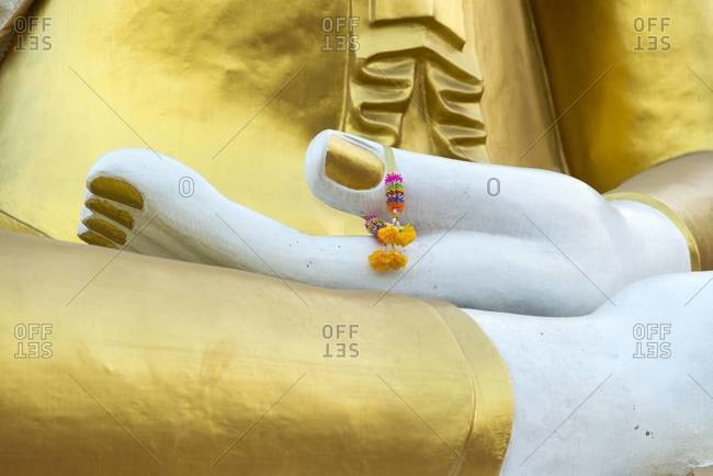 Flowers on the thumb of a Buddha statue in Chiang Mai, Thailand