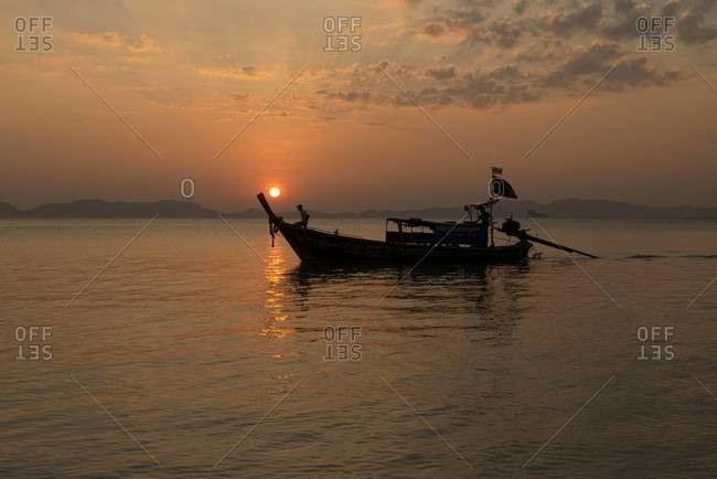 A longtail fishing boat sits on the beach at sunset in Krabi, Thailand