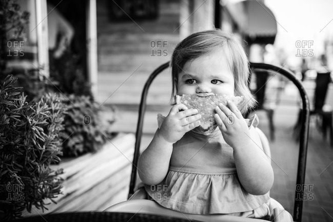 Toddler girl trying to eat a sandwich