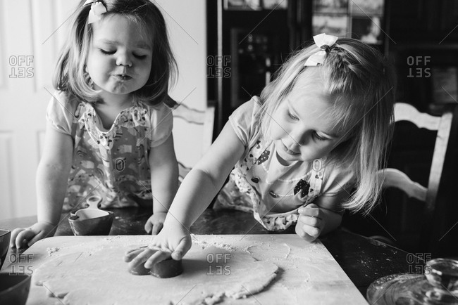Little girls making heart-shaped cookies on Valentine\'s Day