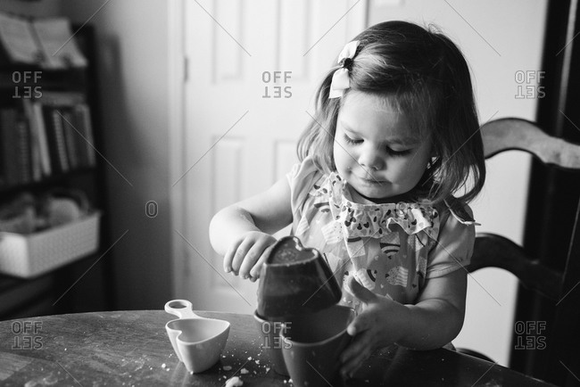 Little girl pouring ingredients into a heart-shaped mold