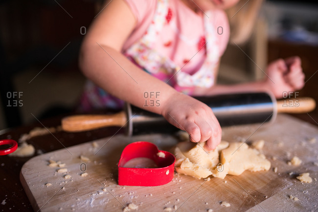 Girl making heart-shaped cookies for Valentine\'s Day