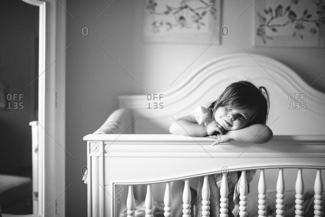 Girl leaning on the railing of her crib