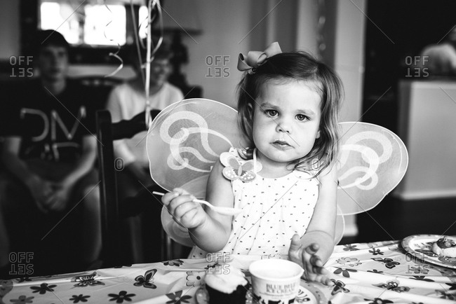 Girl wearing butterfly wings by the table