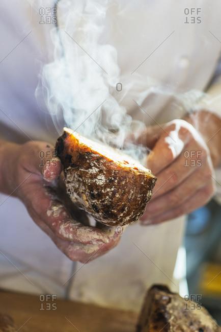 Hands holding freshly-baked bread - Offset