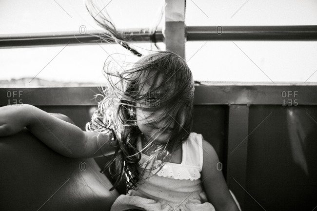 Wind blows of a little girl's hair on a public transport vehicle