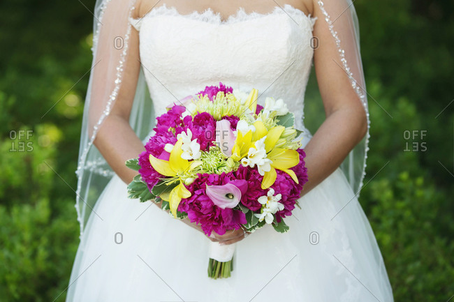 Midsection view of bride holding a bouquet