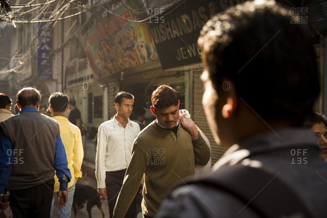 New Delhi, India - March 3, 2014: People walking in a Delhi alley, India