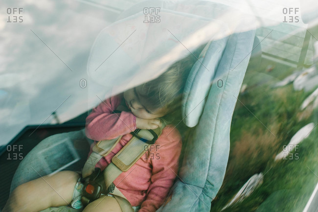 View of little girl sleeping in car