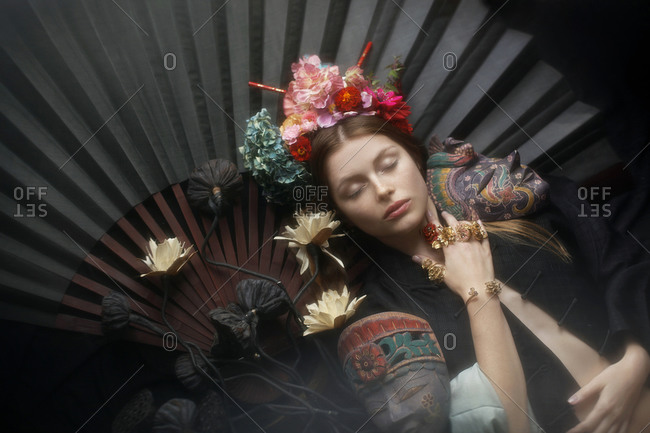 Young woman lying on a hand fan