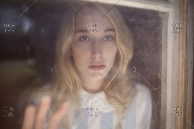 Blonde woman staring out of a dirty window
