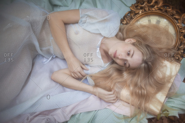 Blonde woman lying on the floor with a book